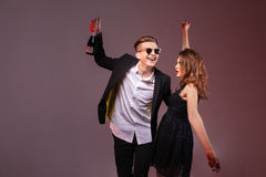 Happy couple holding bottle of champagne and dancing Royalty Free Stock Photography
