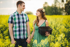 Happy couple holding bu hands and looking each other, face to face and smiling. Handsome boyfriend wearing checked shirt and prett Royalty Free Stock Images
