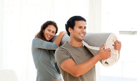 Happy couple holding a carpet together Stock Images