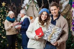Happy Couple Holding Christmas Presents With. Portrait of happy young couple holding Christmas presents with parents standing in background at store Stock Images
