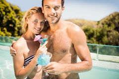 Happy couple holding cocktail. In the pool stock images
