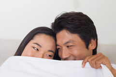 Happy couple holding duvet over face Stock Image