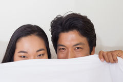 Happy couple holding duvet over face Royalty Free Stock Photo