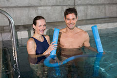 Happy couple holding foam rollers smiling at camera Royalty Free Stock Image