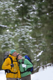 Happy couple holding hands and backpacking in snowy woods royalty free stock images