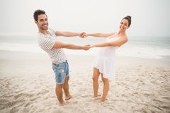 Happy couple holding hands on the beach Stock Photography
