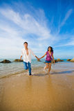 Happy couple holding hands having fun running on t. He beach with bright blue sky Stock Photo