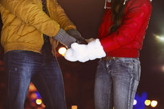 Happy couple holding hands in knitted mittens Royalty Free Stock Images