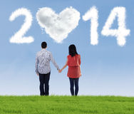 Happy couple holding hands looking in the future. Of new year 2014 Stock Photo
