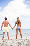 Happy couple holding hands and looking at the sea Stock Photography