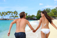 Happy couple holding hands running having fun. Playful on the beach. Young people from behind playing together on summer travel destination tropical holidays royalty free stock image