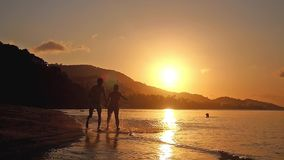 Happy couple holding hands running in tropical beach at amazing sunset in slow motion. 1920x1080 stock footage