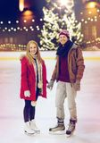 Happy couple holding hands on skating rink Royalty Free Stock Images
