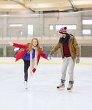 Happy couple holding hands on skating rink Stock Photo