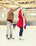 Happy couple holding hands on skating rink Royalty Free Stock Image