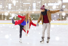 Happy couple holding hands on skating rink. People, friendship, sport and leisure concept - happy couple holding hands on skating rink Stock Photos