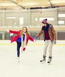 Happy couple holding hands on skating rink. People, friendship, sport and leisure concept - happy couple holding hands on skating rink Royalty Free Stock Photos