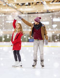 Happy couple holding hands on skating rink. People, friendship, sport and leisure concept - happy couple holding hands on skating rink Stock Image