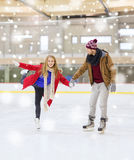 Happy couple holding hands on skating rink Royalty Free Stock Photo