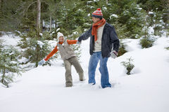 Happy couple holding hands in snowy woods stock photos