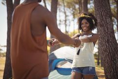 Happy couple holding hands while standing against tent Royalty Free Stock Photo