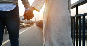 Happy couple holding hands in the sunset royalty free stock photo