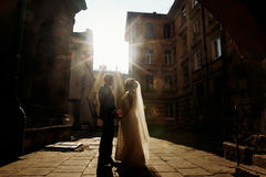 Happy couple holding hands at sunset, newlywed bride and groom p. Osing in sunny european street, stylish husband and wife standing near old buildings Royalty Free Stock Image