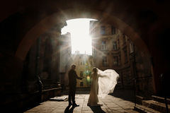 Happy couple holding hands at sunset, newlywed bride and groom p. Osing in sunny european street, stylish husband and wife standing near old buildings Royalty Free Stock Photos