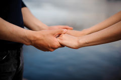 Happy couple holding hands together. Water background Royalty Free Stock Photography