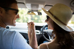 Happy couple holding hands while traveling in car Royalty Free Stock Photo
