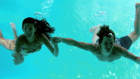 Happy couple holding hands underwater in swimming pool and waving. In slow motion stock video footage
