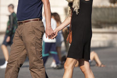 Happy couple holding hands. A happy couple holding hands and walking through the city. Blurred background with other people. Concept of life as a couple Royalty Free Stock Photos