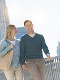 Happy Couple Holding Hands While Walking In City Stock Photography
