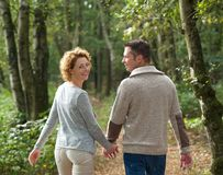 Happy couple holding hands and walking in the forest stock photos