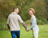 Happy couple holding hands and walking outdoors Stock Photography