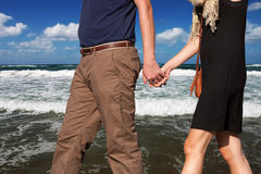 Happy couple holding hands. A happy couple holding hands and A happy couple holding hands walking on the sea shore. Concept of life as a couple Stock Photography