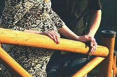 Happy couple holding hands. Happy young couple holding hands on wood railing Stock Photo