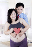 Happy couple holding heart symbol Royalty Free Stock Images