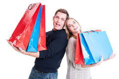 Happy couple holding heavy shopping bags and acting amazed Stock Images