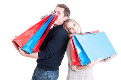 Happy couple holding heavy shopping bags and acting playful Royalty Free Stock Photo