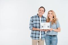 Happy couple holding house model on white Stock Photography
