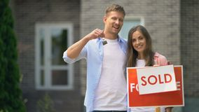 Happy couple holding keys from house near sold sign, mortgage for young families