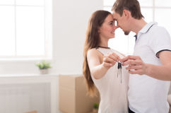 Happy couple holding keys of their new home. Key of new home. Happy young couple standing close to each other and smiling while holding keys from house, copy Royalty Free Stock Photos