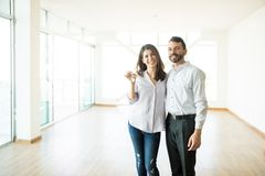 Happy Couple Holding Keys In Their New Home. Happy mid adult couple holding keys in their new home royalty free stock photo