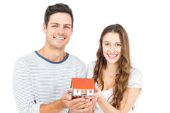 Happy couple holding miniature house Stock Photography