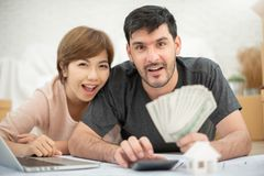 Happy couple holding money and calculating their budget. Happy young couple with laptop holding money and calculating their budget for moving house. Looking at stock image