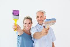 Happy couple holding paintbrushes smiling at camera Royalty Free Stock Image