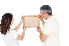 Happy couple holding picture frame Royalty Free Stock Photos
