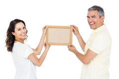 Happy couple holding picture frame Royalty Free Stock Photography