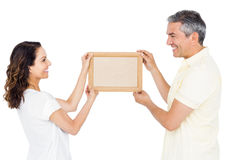 Happy couple holding picture frame Stock Image